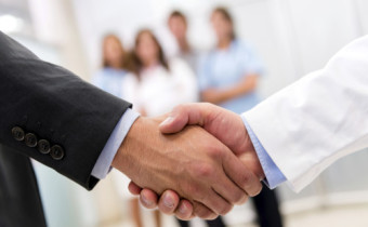 Business man and doctor handshaking over a medical insurance